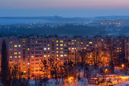 Top view of the evening city in winter with illuminated streets and light in the windows of apartments.