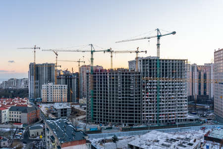 Construction site, cranes and multi-storey unfinished buildings at sunrise or sunset in winter.