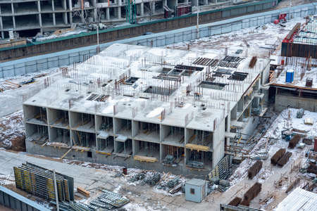 Top view of the construction of a multi-storey building in winter. Stock Photo