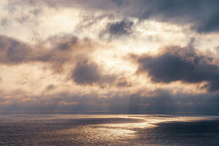The sun's rays make their way through dramatic dark clouds over the sea, patches of light on the water. Stock Photo