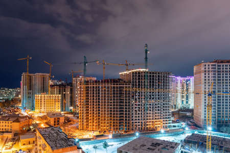 Construction site, cranes and multi-storey unfinished houses at night in winter.