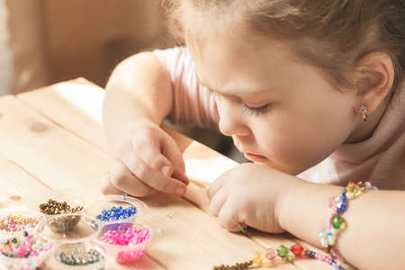A little girl is engaged in needlework, making jewelry with her own hands, stringing multi-colored beads on a thread.