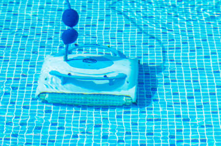 Cleaning the pool bottom with an underwater vacuum cleaner.