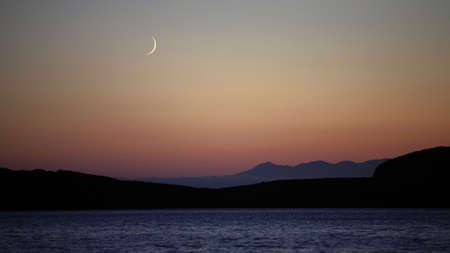 disputed: Sea landscape with mountains and a moon Stock Photo