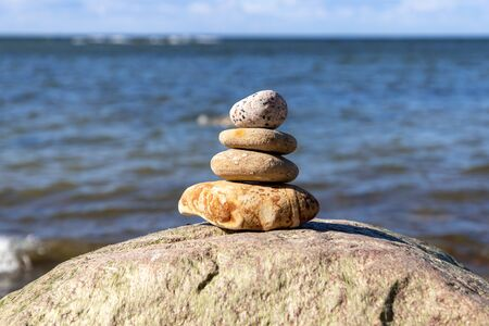 Concept of harmony and balance. Rock zen on a background of a summer beach. Stok Fotoğraf - 148672467