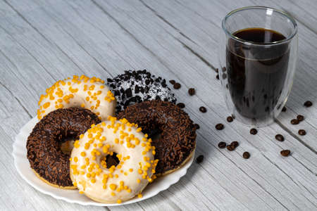 Donuts on a white plate on a wooden table and coffee