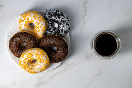 Donuts on a white plate on a marble table and coffee Stok Fotoğraf