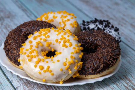 Donuts on a white plate on a wooden table