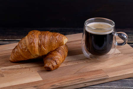 Croissants with a cup of coffee on a wooden board. Stok Fotoğraf