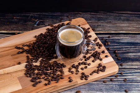 Coffee mug on wooden board and coffee beans