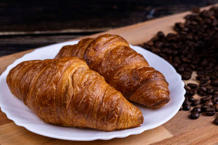 Croissants on a white plate and coffee beans on a wooden board Stok Fotoğraf