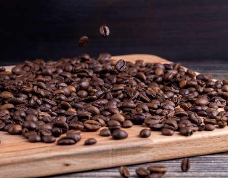 Falling coffee beans on wooden board