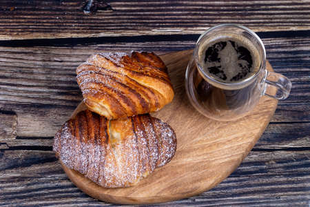 Sweet buns with a cup of coffee on a wooden board.