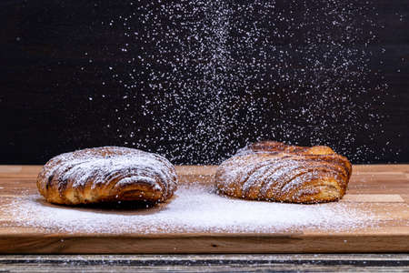 Sweet buns sprinkled with powdered sugar