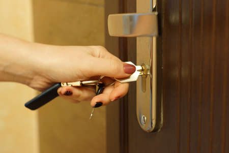 The woman turns the key in the lock on the outside door open