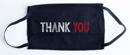 Black disposable protective mask with THANK YOU text on black background.
