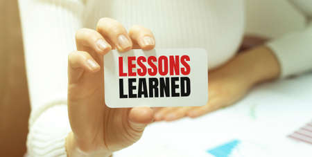 Businesswoman holding a card with text LESSONS LEARNED