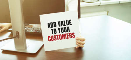 Businesswoman putting a card with text ADD VALUE TO YOUR CUSTOMERS. business concept Foto de archivo - 150360087