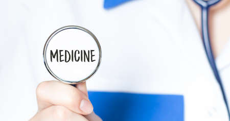 Doctor holding a stethoscope with text MEDICINE, medical concept. business concept 免版税图像 - 150248029