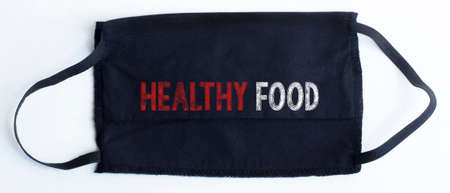 Black disposable protective mask with HEALTHY FOOD text on black background. medical CONCEPT