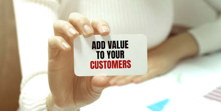 Businesswoman putting a card with text ADD VALUE TO YOUR CUSTOMERS. business concept