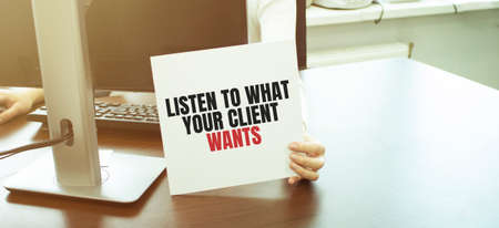 Businessman putting a card with text LISTEN TO WHAT YOUR CLIENT WANTS. business concept