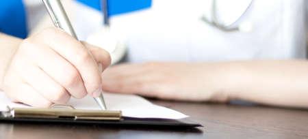 Hand of female doctor with pen writing on prescription blank 免版税图像