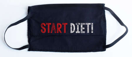 Black disposable protective mask with start diet text on black background.