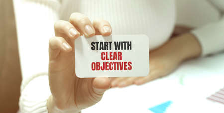 Businesswoman holding a card with text START WITH CLEAR OBJECTIVES. business concept Reklamní fotografie