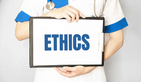 Doctor holding a card with text ETHICS, medical concept Stock Photo