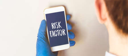 Hand in medical glove holding smartphone on white background. Blank screen with risk factor text.