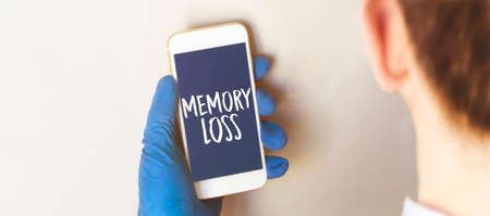 Hand in medical glove holding smartphone on white background. Blank screen with memory loss text.