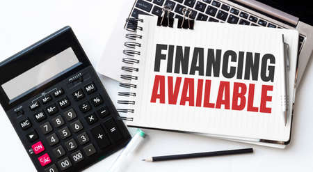 Keyboard of laptop, calcualtor, pencil and notepad with text financing available on the white background