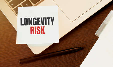 Laptop, pen and notepad sheet with text LONGEVITY RISK