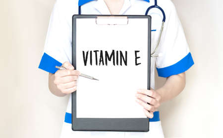 Doctor's hands with pan and paper plate, stethoscope and keyboard on the white background. VITAMIN E.