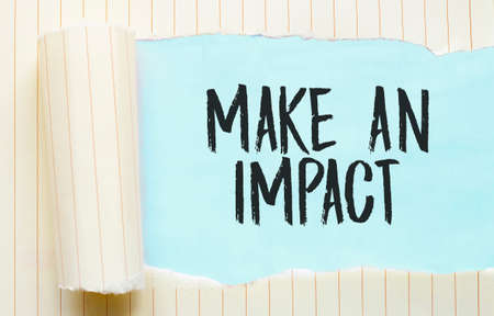 The text MAKE AN IMPACT appearing behind torn white paper