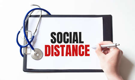 Text SOCIAL DISTANCE on the paper plate with stethoscope, Medical concept