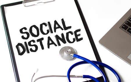 word SOCIAL DISTANCE on the paper plate with stethoscope, Medical concept