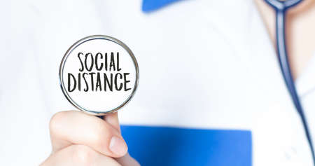 SOCIAL DISTANCE sign and hand with stethoscope of Medical Doctor