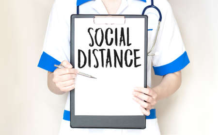 Doctor write word SOCIAL DISTANCE on the paper plate with stethoscope, Medical concept Banque d'images