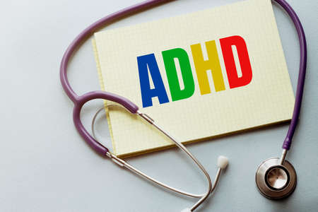 On a purple background a stethoscope with yellow list with text ADHD