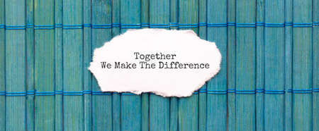 TOGETHER WE MAKE THE DIFFERENCE text on the piece of paper on the green wood background