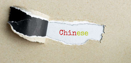 The text Chinese appearing behind torn brown paper Foto de archivo