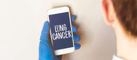 Hand in medical glove holding smartphone on white background. Blank screen with lung cancer text. 版權商用圖片