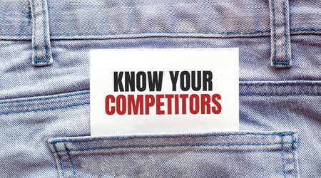 KNOW YOUR COMPETITORS, words on a white paper stuck out from jeans pocket. Business concept