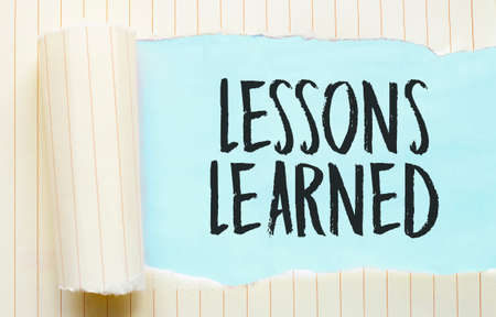 The text LESSONS LEARNED appearing behind torn white paper