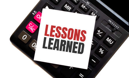 calculator with text LESSONS LEARNED with white paper