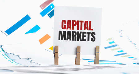 CAPITAL MARKETS text on paper sheet with chart, dice, spectacles, pen, laptop and blue and yellow push pin on wooden table - business, banking, finance and investment concept