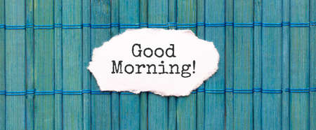GOOD MORNING text on the piece of paper on the green wood background