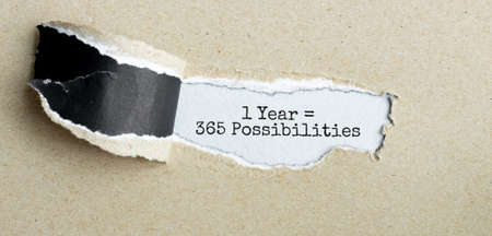 The text 1 year is 365 opportunities appearing behind torn brown paper